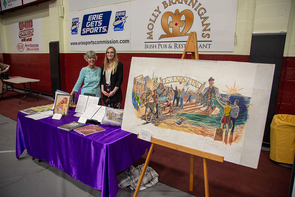 Student and Faculty member pose by Mural at Celebrate Gannon